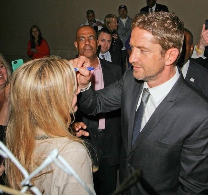 Gerard Butler Autographs a Fan's Forehead (3 pics)