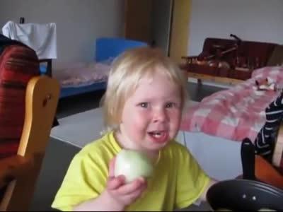 Маленькая девочка любит есть лук
