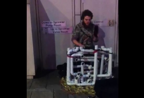 Street Musician Playing On A Weird Hand-Made Instrument