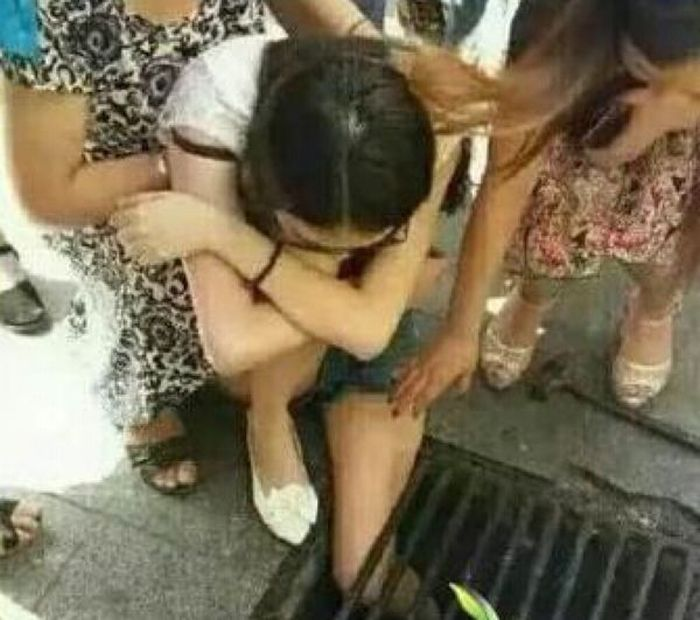 Chinese Girl Gets Stuck In A Drain Because She Was Texting While Walking (2 pics)