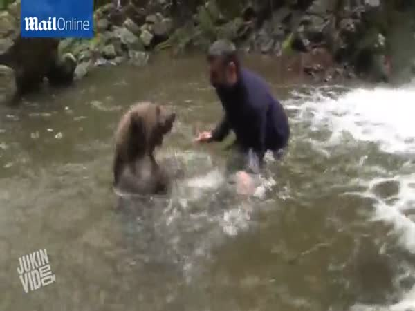 Rare Footage Captures Playful Exchange Between Man And Huge Bear As They Embrace After A Friendly Water Fight