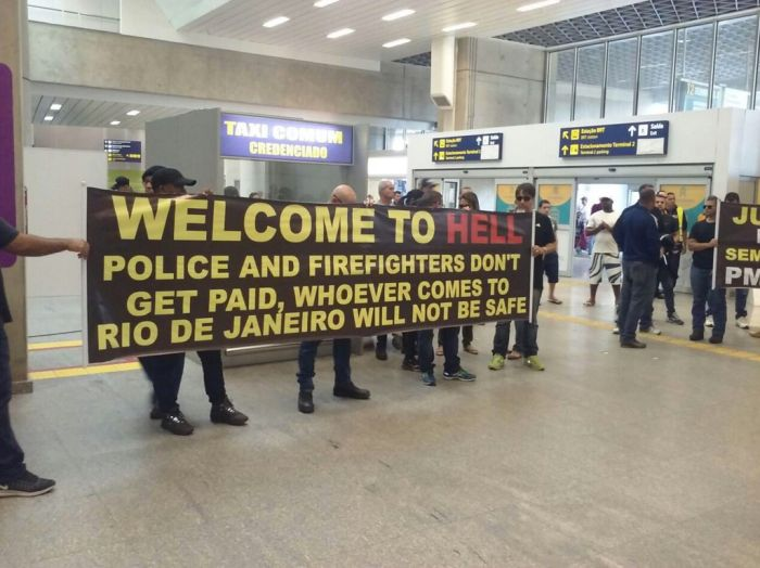 Citizens Of Rio Greet Visitors With A Welcome To Hell Banner (2 pics)